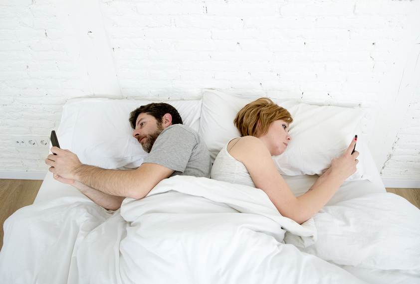 sad view of young married couple using their mobile phone in bed ignoring each other as strangers in relationship and communication problems and internet social network addiction